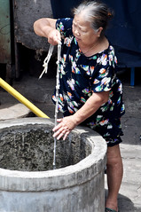 Forget the tap... (Roving I) Tags: street water vertical women working lifestyle wells vietnam elderly aged ropes knots danang