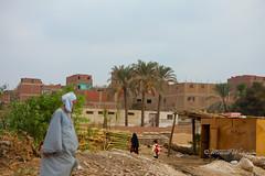 Man in Giza (Sound Quality) Tags: africa travel people woman man architecture canon reeds landscape town tour village veil african egypt streetphotography egyptian giza baladi beladi canon50d michaelwashington spirit7628yahoocom httpwwwtumblrcomblogsoundquality