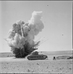 A discarded Italian bomb is blown up beside a Matilda tank near Tobruk. The resulting craters were used to hide the tanks, 15 October 1941.