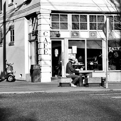 Surfing the Net Outside (A-Dubb2012) Tags: man table cafe laptop streetsign streetphotography trashcan moped nex6