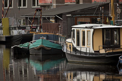 Motorboats in the Amsterdam canal alongside a houseboat (float boat) (Kitty Terwolbeck) Tags: black holland reflection green netherlands amsterdam river boot boat canal colorful riverside nederland houseboat canals colourful motorboat gracht reflectie entrepotdok woonboot motorboot floatboat