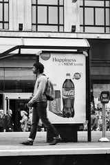 Oblivious to happiness (Trevor King 66) Tags: street blackandwhite bw manchester nikon walk kitlens advert cocacola tramstop stride d3100