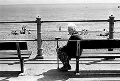 4 (Adam Turner 96) Tags: shadow sea blackandwhite sun beach lady 35mm bench sand kodak tmax grain rail pentaxk1000 lonely hastings