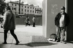 Utopia on Euston Road (yorktone) Tags: road street shadow portrait blackandwhite bw woman man london eye art monochrome hat sunshine st fur lumix photography photo newspaper candid coat hard streetphotography commuter contact g3 pancras euston seller workman yorktone