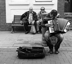 'He's playing our tune' (Andy WXx2009) Tags: street people urban blackandwhite musician men monochrome sunglasses wales shopping bench europe sitting candid livemusic performance streetphotography meeting buskers bags accordian streetartists porthcawl