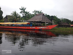 Boat near Amazonian river tribe houses a few miles up from the river's mouth of Nauta, Iquitos, Peru. (okaystephanie) Tags: trees peru water river season high amazon rainforest native traditional culture palm canoe roofs rainy tribe iquitos amazonas thatched amazonian nauta peruvians