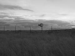 Blowin' in the wind (snappytiger) Tags: sky blackandwhite west nature windmill grass clouds fence rust horizon barbedwire weathered farms wyoming prairie plains backroads cheyenne