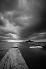 Island Bay (buddythunder) Tags: blackandwhite bw storm clouds sunrise landscape moody timber jetty perspective wave wideangle knot symmetry wharf wellington balance islandbay sawn leadin