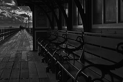 Braving The Storm - Southend Pier (Feggy Art) Tags: uk winter sea england sun white storm black building abandoned beach water monochrome thames train walking coast pier couple decay victorian estuary east seats february shelter stark setting derelict essex southend decaying