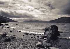 Loch Ness (JB Morlot) Tags: uk sky mountain lake heritage film beach monochrome sepia clouds mediumformat hope scotland countryside vanishingpoint highlands fishing solitude loneliness fuji decorative space faith fineart hunting pebbles calm fate zen destiny serenity huge duotone 6x9 dreamy nordic meditation loch wilderness relaxation eternity largeformat mystic timeless lochness endless otherworld fujigsw690iii illimited