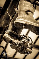 Henry is taking a rest, sitting on a log, dangling his feet. (Nataraj Metz) Tags: italien italy museum cuerda boot spur shoes europa europe italia european boots rope hanging crampon hang schuhe italie rubberboots gummistiefel botte botas emiliaromagna corde corda stiefel seil europen hngen europeo colgar pendre cavo soragna regenstiefel europisch steigeisen crampn milieromagne bottedepluie  climbingiron  museodelparmigiano climbingspur parmesanmuseum lasbotasdeagua