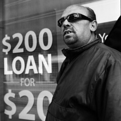 """One-eye Sunglasses (2) - Legalized Loan Sharks by Man-Wei - Continue from Part 1.  After we crossed the stop light, we ended up chatting in front of Cash Money, one of those payday advance establishments.   I said to him, """"We sure can use that $200!"""" """"These %$@# blood suckers. They're bunch of legalized loan sharks!"""", he blasted. I took one more picture of him and that was when we parted ways.  I'm curious what is the situation with these payday loans and here is an example of borrowing $300 for two weeks. 1. The loan must be paid in full on or before the scheduled due date, 14 days. 2. There is a fee of $63 for $300 loan. So the immediate total cost to borrow $300 is $363.  That is like an annual rate of 547.5% during those 14 days. 3. In the event of default, borrowers will be charged a returned item fee of $40 plus interest at a rate of 60% per annum.  Even cash advance on my credit cards is better than this!  Well, they are getting away with this is because the Canadian Government has let loans under $1,500 exempted from the maximum interest rates allowed under the Criminal Code.  And these establishments specifically prey on certain demographics who have no other means to borrow money.  Rolleiflex Automat MX Zeiss Tessar f/3,5 Kodak TMAX 400 (EI 800), TMAX Developer (1:9), CanoScan 9000F"""