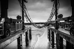 Boat Hoist (Myrialejean) Tags: sea sky blackandwhite industry wet water monochrome weather vent boat fishing exposure track mechanical cloudy loop harbour outdoor wheels pipes engine tire structure grill salty maritime infrastructure rails motor ladder railing posts winch functional trawler tyre bridlington ce cradle striker