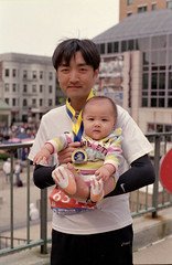 Proud (dtanist) Tags: family baby film boston analog pose 50mm pentax marathon massachusetts father medal 400 walgreens smc ricoh pentaxm xrm