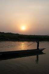 Chitwan Boat at Sunset (William J H Leonard) Tags: park travel nepal sunset portrait sky sun man colour travelling water silhouette river skyscape landscape asian boat nationalpark asia sundown candid bank portraiture nepalese chitwan boatman nepali southasia southasian travelphotography chitwannationalpark candidportraiture chitwandistrict chitwanvalley