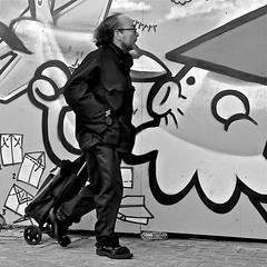 Airkiss (Akbar Simonse) Tags: street urban bw man holland blancoynegro netherlands monochrome square graffiti zwartwit sandals trolley candid nederland streetphotography denhaag bn thehague straat sandalen tegenwind lahaye sgravenhage agga straatfotografie headwind kbtr akbarsimonse panasonicdmcfz38 vision:outdoor=089 aitkiss luchtzoen