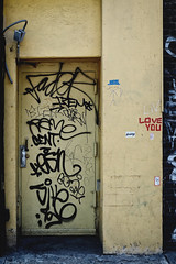mixed messages. (jdx.) Tags: door nyc newyorkcity streetart eastvillage newyork abstract color art love outdoors graffiti downtown moody fuji outdoor tag lowereastside streetphotography documentary gritty doorway bowery grainy tagging graffitiart jdx fujixe2 moodygrams