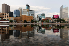 Minneapolis Rain. (Urban Camper.) Tags: reflection water rain minnesota architecture clouds buildings puddle photography rainyday streetphotography minneapolis overcast twincities urbanphotography minneapolisminnesota minneapolisskyline minneapolisphotographer urbancamperphotography