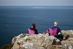 Enjoy The Silence (claudiopro) Tags: pink sea howth cliff woman sun seascape man chair couple rocks day head walk horizon fuchsia sunny glorious silence enjoy binn adair