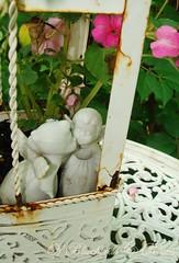 A Stolen Kiss (Bluebird Becca) Tags: pink flowers white birdcage metal gardens angel garden table rust kiss couple iron secret rustic rusty angels cherub enchanted cherubs impatiens impatien