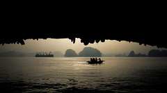 inside the cave looking out (BoXed_FisH) Tags: travel sunset sea vacation mountains silhouette bay boat nice cliffs vietnam limestone fujifilm tanker overseas x100 halung