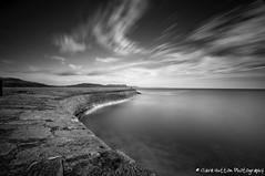 (Claire Hutton) Tags: uk winter sea england people blackandwhite bw motion water monochrome clouds mono coast seaside movement wideangle cliffs coastal dorset curve streaks figures wispy lymeregis goldencap thecobb ndfilter jurassiccoast leadin 10stop nd110 bw110 leefilters nikond90 tamron1024mm 06he