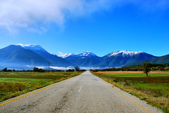 The infinite (jimiliop) Tags: road travel blue trees winter sky snow mountains green grass lines yellow fog way landscape countryside long bright pavement geometry horizon perspective sunny clear greece fields straight far tops infinite bold peloponese corinthia  stymfalia