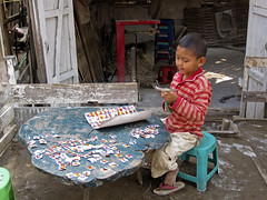 A young boy in Pyinmana Township does a crafts project (World Bank Photo Collection) Tags: boy project bench table cut burma craft scissors myanmar activity worldbank eastasia pyinmanatownship