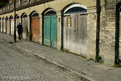 Man in black walking past garages underneath road (Roberto Herrett) Tags: road city uk england man london english k horizontal walking doors unitedkingdom britain pavement capital cities arches cobbled richmond u colored british cobbles coloured muted stockphoto garages rherrettflk