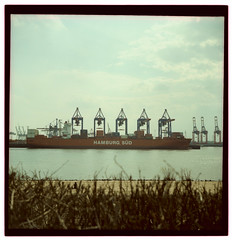 A woman sitting alone on Elbstrand watching cranes loading a container ship (-ciaran) Tags: 120 6x6 film tourism beach strand port docks mediumformat square xpro harbour crossprocess hamburg terminal cargo cranes container lubitel hh containership shipping solitary elbe elbstrand obvious hanseatic deepwater provia100 hamburgsd othmarschen everybodyhatesatourist