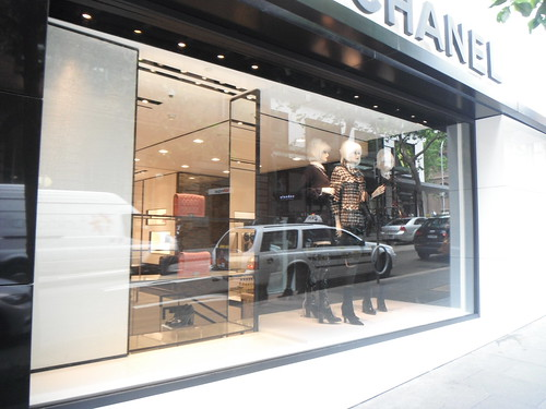 door city trees cars window fashion shop reflections logo lights mannequins boots display pavement taxi sydney australia nsw heels handbags hautecouture chanel jackets apparel vision:outdoor=0507