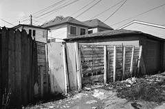 Fence on Fence (geowelch) Tags: toronto blackwhite garage fences 35mmfilm laneway urbanlandscape pentaxmx urbanfragments xp2super400 rogersroad plustekopticfilm7400 pentaxtakumara28mm28