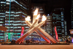 Vancouver Olympic Cauldron (Patrick Lundgren) Tags: world plaza city winter light red urban orange canada west building tower night vancouver canon dark square landscape jack fire lights coast long exposure downtown cityscape bc place darkness pacific northwest harbour torches centre low sigma center columbia flame torch convention british olympic olympics coal shaw cauldron poole paralympics vancity landsacpe vision:outdoor=0572 vision:sky=0547