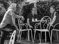 A Street Conversation (3) (BW) (Olympus OMD EM5II & mZuiko 12-40mm f2.8 Pro Zoom (markdbaynham) Tags: street people island greek town zoom candid group hellas evil olympus greece pro gr f28 omd csc mz limnos hellenic m43 zd mft lemnos myrina em5 1240mm mirrorless micro43 micro43rd mzuiko em5ii zuikolic
