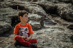 Sitting amongst fire (Melissa Maples) Tags: boy turkey fire grey kid nikon rocks asia child flames trkiye can nikkor chimera vr afs  chimaira 18200mm  f3556g yanarta  18200mmf3556g iral d5100
