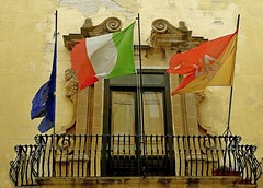 flags 'n rags (breboen) Tags: door old building history window fence fly official iron europe colours symbol wind rags decay balcony formal eu wave flags pole national sicily torn drape tear ochre damaged trapani shred degraded wrenched