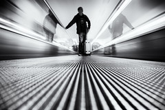 tripping (polo.d) Tags: trip travel white motion black blur monochrome silhouette speed point airport long exposure view low rail luggage traveller automatic passenger