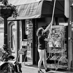 Raising the flag (John Riper) Tags: street bw woman white black netherlands girl monochrome shop lady canon john square photography mono basket zwartwit candid newspapers bikes bicycles l hanging stick kiosk magazines telegraaf gouda 6d 24105 straatfotografie riper johnriper photingo