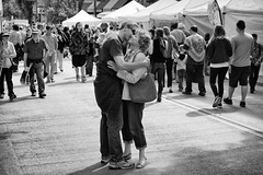 Just A Hug & Kiss (John Westrock) Tags: people blackandwhite bw canon streetphotography 7d washingtonstate streetfair udistrict sigma35mmf14