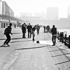 shoot out over the puddle (city/human/life) Tags: bridge light blackandwhite bw sun sunlight white black sunshine buildings reflections river germany puddle deutschland grey spring nikon wasser afternoon fotograf leute photographer shadows bright candid streetphotography himmel talk grau scene menschen promenade skateboard nrw sw skater mann shooter discussion brcke fluss