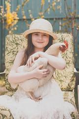 Anna and Lillian (Kilkennycat) Tags: portrait pet white chicken hat animal canon children sitting child dress 50mm14 hen seated backyardchicken 500d pullet kilkennycat t1i ryanconners