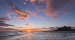 Bamburgh Castle (Jeff Nolan's Photos) Tags: autumn sea cloud sun castle beach silhouette rural dawn coast seaside europe unitedkingdom country style northumberland lowtide bamburgh function masonary