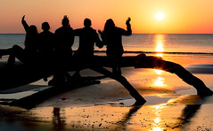 Sunrise and Good Morning Fun (Charles Opper) Tags: light people sun color beach nature water silhouette sunrise canon georgia landscape fun spring sand warm driftwood jekyllisland boneyardbeach