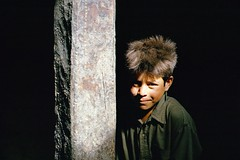 Karimabad, Hunza Valley, Pakistan, 1988 (Photox0906) Tags: pakistan light boy shadow portrait smile childhood youth dark hair noir child lumire pillar young ombre jeunesse sombre valley innocence column hunza enfant sourire karimabad garon colonne pilier jeune valle enfance agakhan pakistanais pakistanese