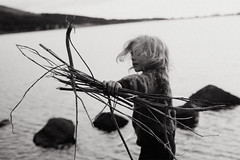 The gatherer (Dalla*) Tags: boy portrait bw white lake black wool nature grass outside sweater kid sticks child wind stones dry pebbles throw throwing gatherer icelndic dallais