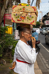 Senior woman with basket on the head (Evgeny Ermakov) Tags: street old travel decorations red people bali woman white holiday tourism senior colors fashion yellow indonesia asian temple holidays asia southeastasia hand head candid traditional decoration ceremony culture style scene newyear clothes celebration exotic destination ritual local southeast typical cultural ubud touristic balinese nyepi dayofsilence editorialuse