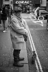 Soho Man Walking His Cat - London Street Photography (Nicholas Goodden) Tags: old city people urban bw man london coral cat walking photography 50mm candid sony soho citylife streetphotography age londres streetphoto leash unposed lead londra nokton urbanlife urbanphotography f15 flatcap londoners streetphotographer photoderue notposed streetsoflondon urbanphotographer mirrorless voigtalnder walkinghiscat a7rii