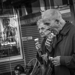 On a street in Manchester (BazM:Photog.......900k views!) Tags: street people blancoynegro monochrome square manchester blackwhite couple northwest noiretblanc icecream streetphoto twopeople peoplewatching oldcouple streetcandid northwestengland streetcapture twooldpeople
