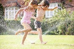 Two Children Running Through Garden Sprinkler (Tonya B4) Tags: boy summer playing male wet water girl grass smiling horizontal female laughing garden children fun outside happy child action outdoor sister brother son running together sprinkler sibling swimsuit twopeople spraying havingfun caucasian splashing swimmingcostume 5yearold unitedkingdomofgreatbritainandnorthernireland