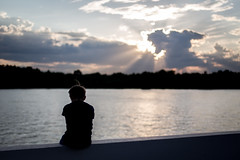 Sorrow (Indigo_Flow) Tags: sorrow boy river evening sun clouds sky water lights reflection lonely